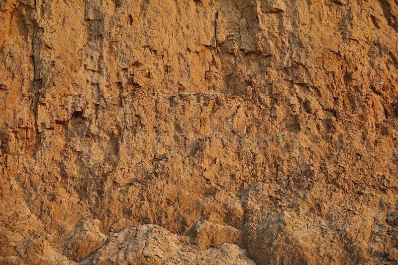 Textuur van de muur van het kleizand van rode kleur met veel barsten van verschillende diepte stock foto
