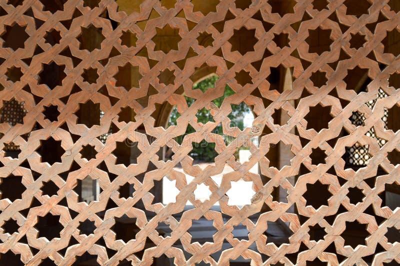 textuur van een houten bruine oude mens van een oud mooi gesneden geweven Arabisch Islamitisch Islamitisch venster met ornamenten stock afbeeldingen