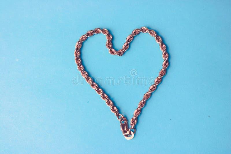 Textuur van een mooie gouden beste feestelijke ketting van het unieke weven in de vorm van een hart op een blauwe ruimte als acht stock foto's