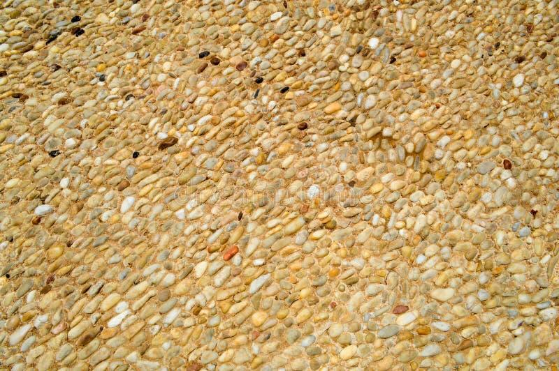 Textuur van een steenmuur, wegen van kleine ronde en ovale stenen met zand met naden van natuurlijke oude gele zwarte bruin Achte stock foto