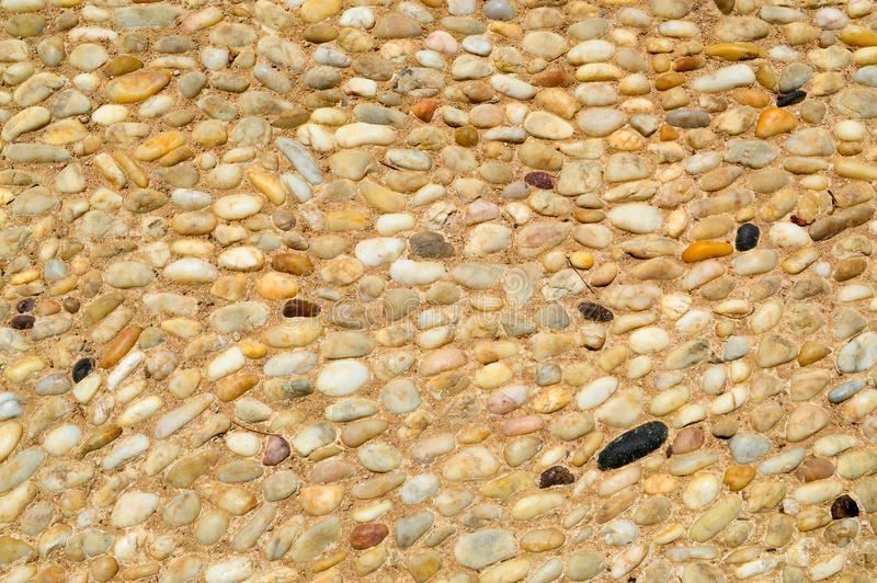 Textuur van een steenmuur, wegen van kleine ronde en ovale stenen met zand met naden van natuurlijke oude gele zwarte bruin Achte royalty-vrije stock foto's
