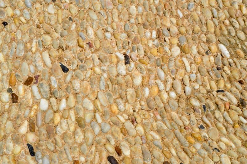 Textuur van een steenmuur, wegen van kleine ronde en ovale stenen met zand met naden van natuurlijke oude gele zwarte bruin Achte stock afbeeldingen