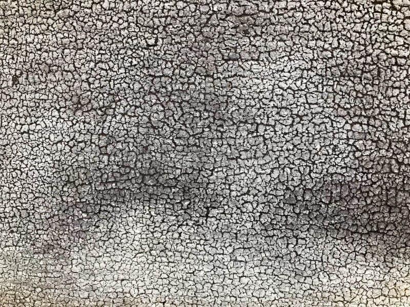 Textuur van een zwarte grijze oude dilapidated concrete muur met stukken van oude sjofele afgebladderde verf met barsten, aders stock fotografie
