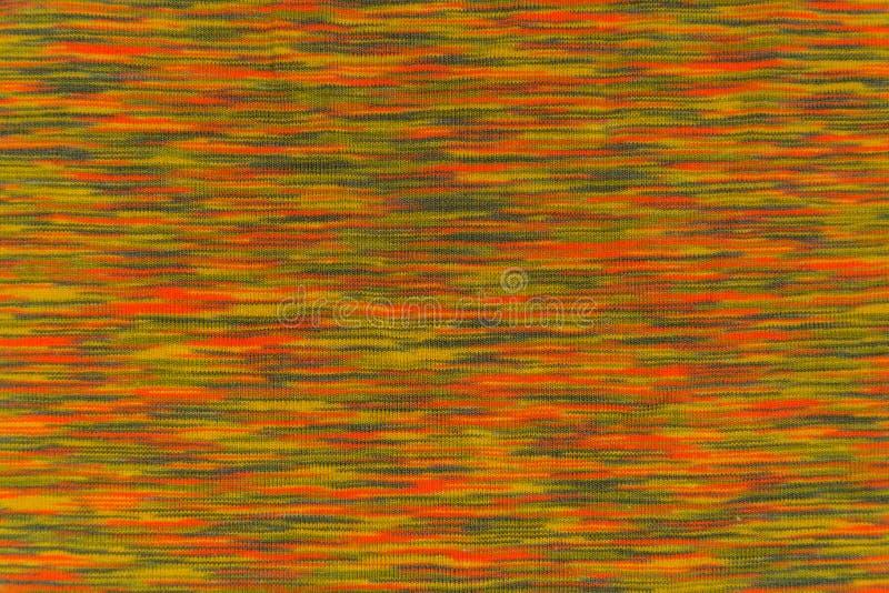 Textuur van gevlekte stof met oranje en groene aanrakingen royalty-vrije stock afbeelding