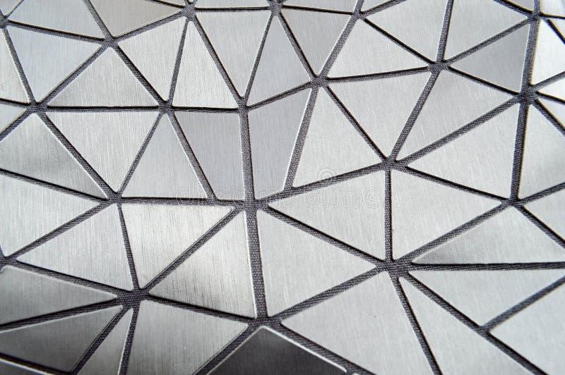 Textuur van grijze gesneden gevormde plastic driehoeken met rond gemaakte hoeken en lijnen De achtergrond stock afbeelding