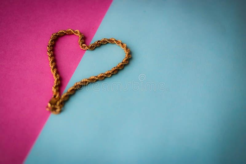 Textuur van het mooie gouden feestelijke ketting unieke weven in de vorm van een hart op een roze purpere blauwe ruimte als achte royalty-vrije stock afbeeldingen