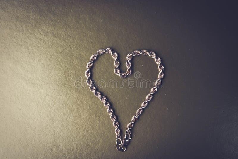 Textuur van het mooie gouden feestelijke ketting unieke weven in de vorm van een hart op een zwart-witte plaats als achtergrond e stock foto's