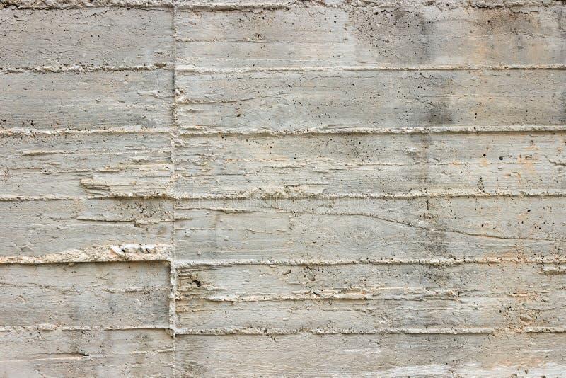 Textuur van houten die bekisting op een ruwe concrete muur als bac wordt gestempeld stock afbeelding