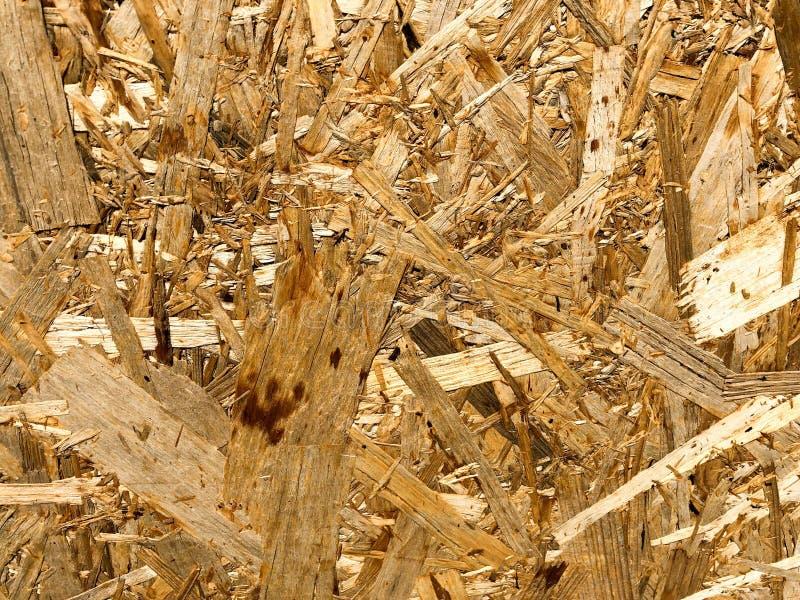 Textuur van houten geel bouwmateriaal van spaanders en samengeperst zaagsel OSB, het afval van de meubilairproductie De achtergro royalty-vrije stock afbeeldingen