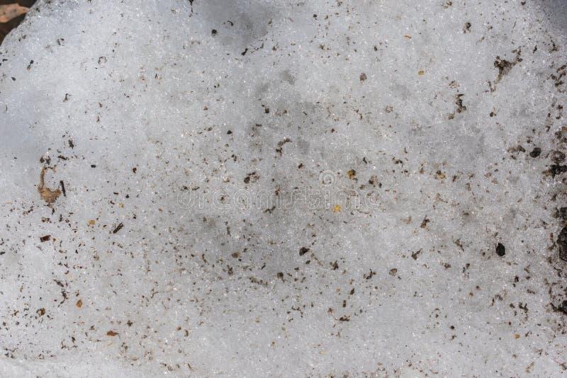 Textuur van ijzige sneeuw met beetjes vuil en bladeren royalty-vrije stock afbeeldingen