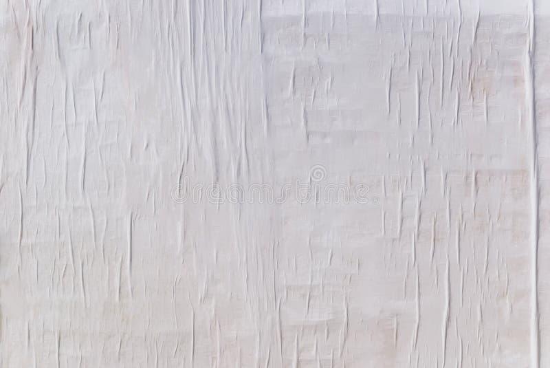 Textuur van nat wit gevouwen document op een openluchtaffichemuur, verfrommelde document achtergrond stock foto's