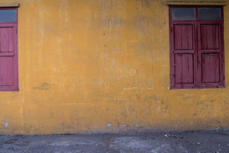 Textuur van oude gele uitstekende muur van industriële fabriek met houten vensters stock afbeeldingen