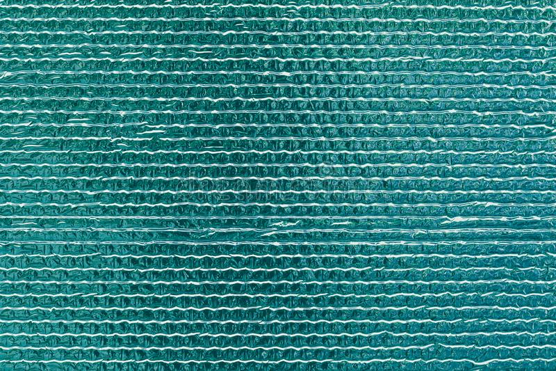 Textuur van turkooise weerspiegelende glanzende muur Glanzende groene folieachtergrond De samenvatting schittert patroon Weerspie stock foto's
