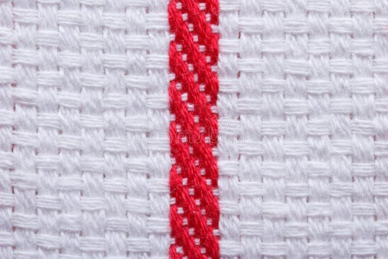 Textuur van witte katoenen keukenhanddoek met een rode streep. Macro. royalty-vrije stock afbeeldingen