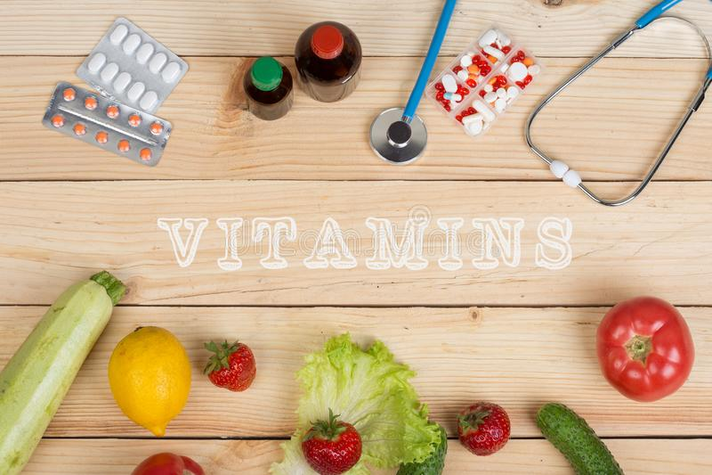 Textvitaminer, naturliga vitaminer, grönsaker, frukter och bär och minnestavlor, piller och stetoskop royaltyfria bilder