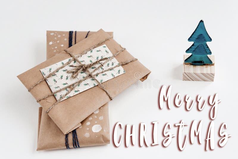 Textzeichen der frohen Weihnachten auf Verzierungsbaum und Geschenke in Handwerks-PA lizenzfreie stockfotografie