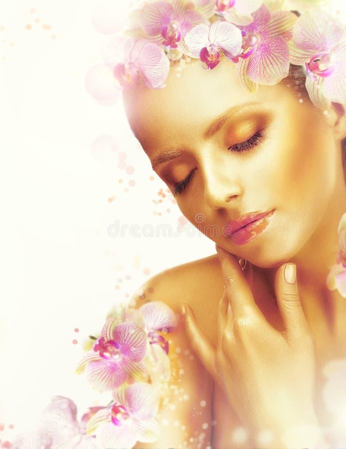 Tez Mujer magnífica con las flores bronceadas perfectas de la piel y de la orquídea fragancia foto de archivo libre de regalías