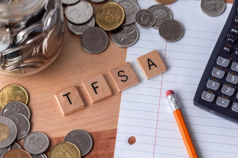 `TFSA` Tax Free Savings Account spelled out in wooden letter tiles. With money, pencil, paper, and calculator surrounding the word stock photo