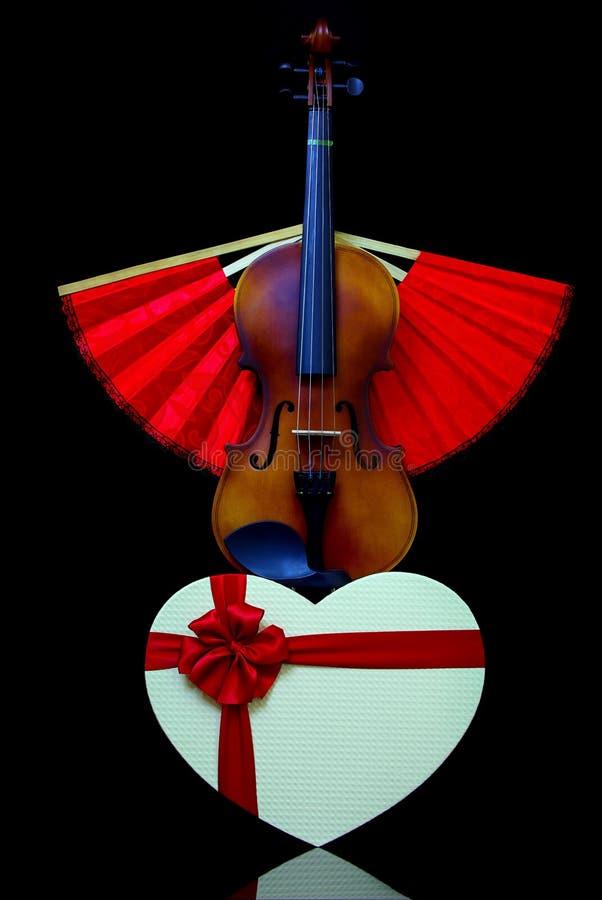 Thème d'amour avec violon, boîte cadeau en forme de coeur et ventilateur de pliage rouge photographie stock