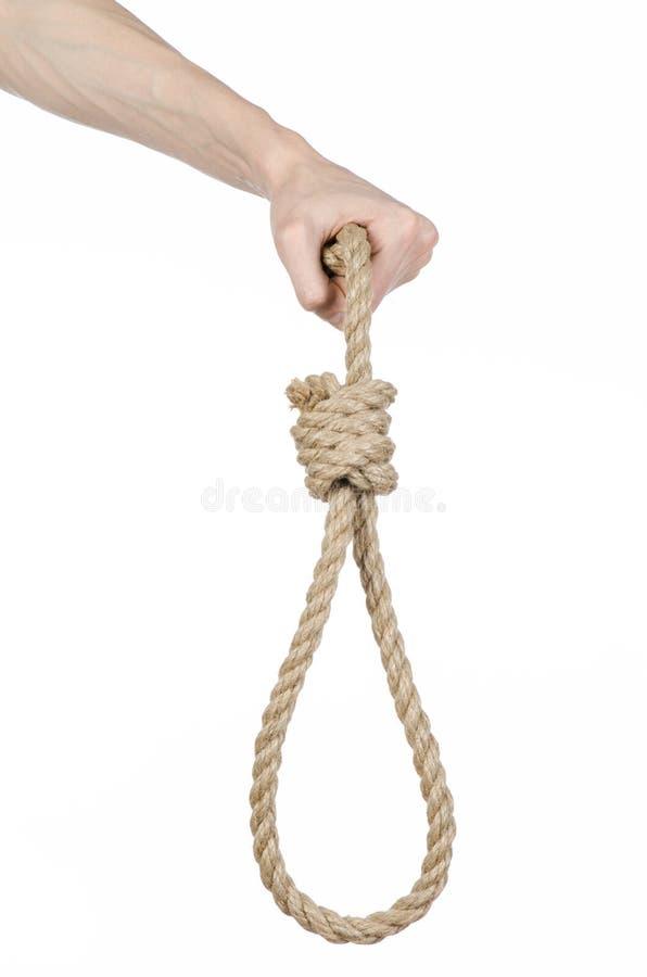 Thème de lynchage et de suicide : la main de l'homme tenant une boucle de corde pour accrocher sur le blanc a isolé le fond photo stock