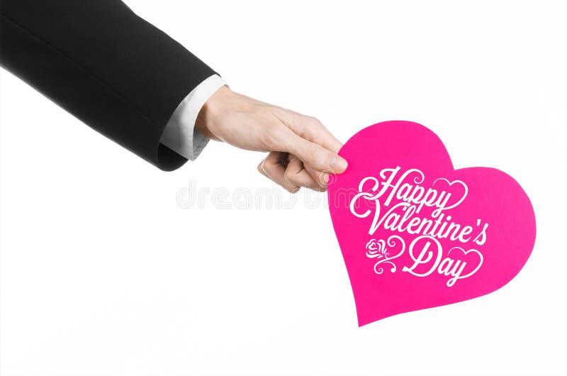 Thème de Saint-Valentin et d'amour : la main de l'homme dans un costume noir tenant une carte sous forme de coeur rose photographie stock libre de droits