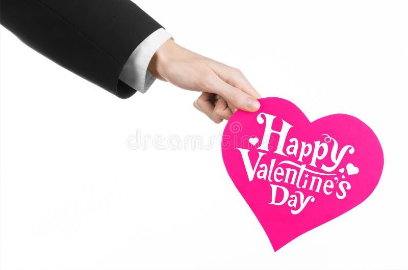 Thème de Saint-Valentin et d'amour : la main de l'homme dans un costume noir tenant une carte sous forme de coeur rose photographie stock