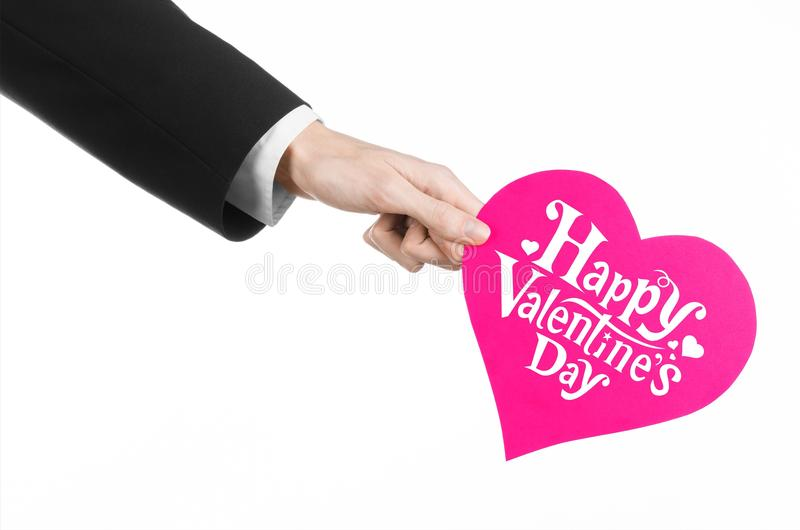 Thème de Saint-Valentin et d'amour : la main de l'homme dans un costume noir tenant une carte sous forme de coeur rose photos stock