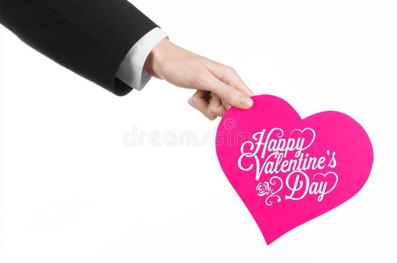 Thème de Saint-Valentin et d'amour : la main de l'homme dans un costume noir tenant une carte sous forme de coeur rose photos libres de droits