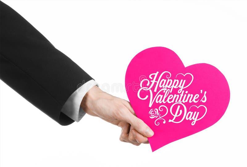 Thème de Saint-Valentin et d'amour : la main de l'homme dans un costume noir tenant une carte sous forme de coeur rose photo stock