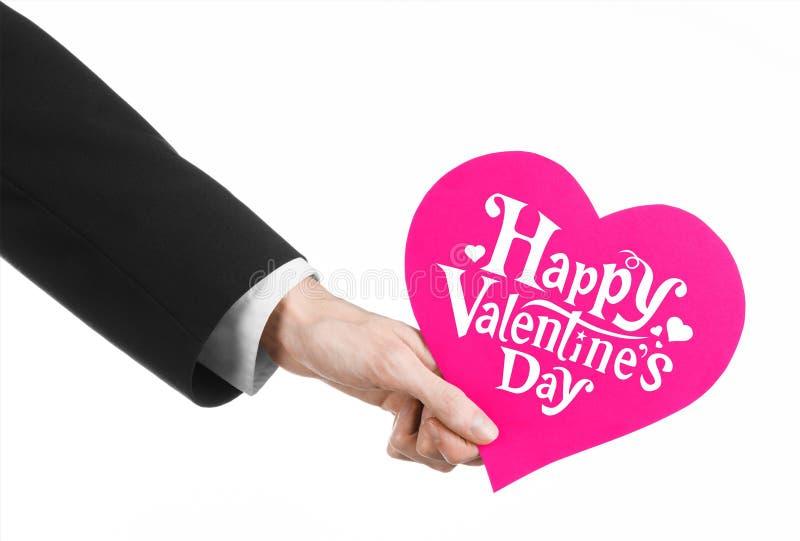 Thème de Saint-Valentin et d'amour : la main de l'homme dans un costume noir tenant une carte sous forme de coeur rose image stock