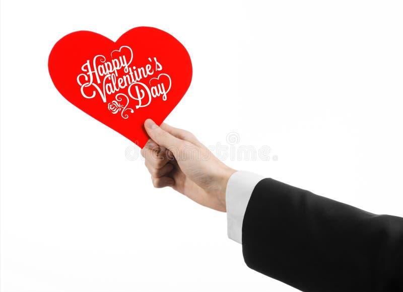 Thème de Saint-Valentin et d'amour : la main de l'homme dans un costume noir tenant une carte sous forme de coeur rouge photographie stock