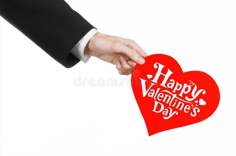 Thème de Saint-Valentin et d'amour : la main de l'homme dans un costume noir tenant une carte sous forme de coeur rouge image stock