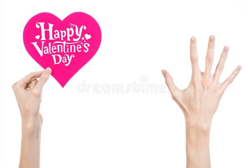 Thème de Saint-Valentin et d'amour : la main tient une carte de voeux sous forme de coeur rose avec la Saint-Valentin heureuse de image stock