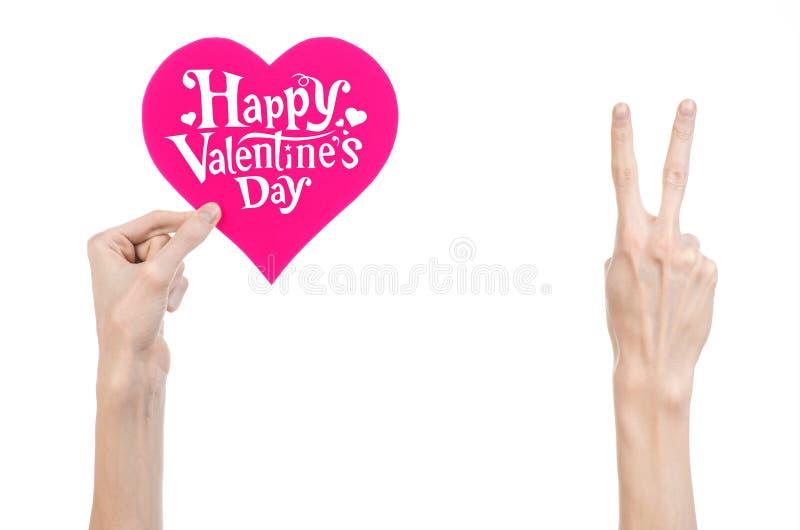 Thème de Saint-Valentin et d'amour : la main tient une carte de voeux sous forme de coeur rose avec la Saint-Valentin heureuse de image libre de droits