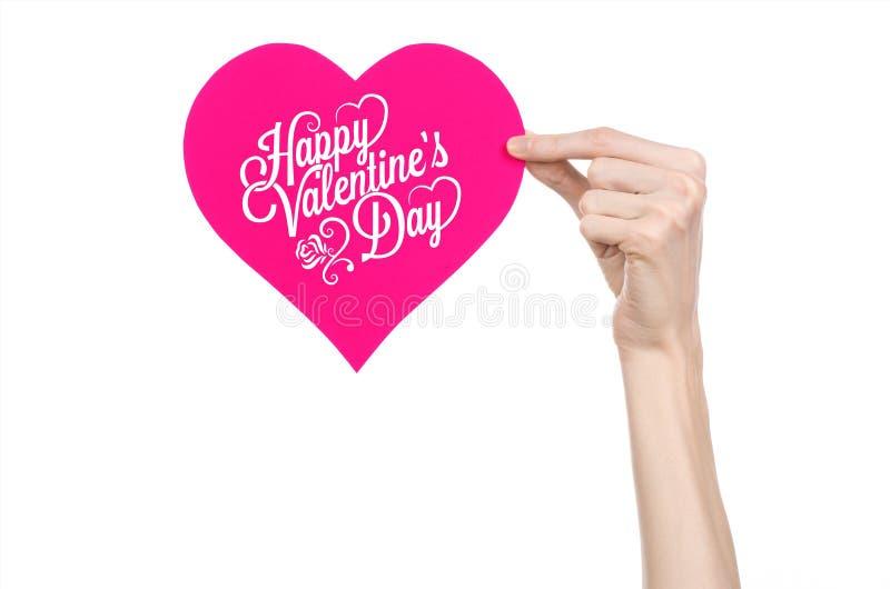 Thème de Saint-Valentin et d'amour : la main tient une carte de voeux sous forme de coeur rose avec la Saint-Valentin heureuse de photographie stock