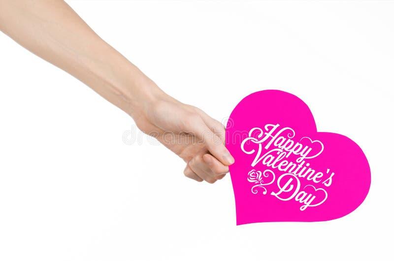 Thème de Saint-Valentin et d'amour : la main tient une carte de voeux sous forme de coeur rose avec la Saint-Valentin heureuse de images stock