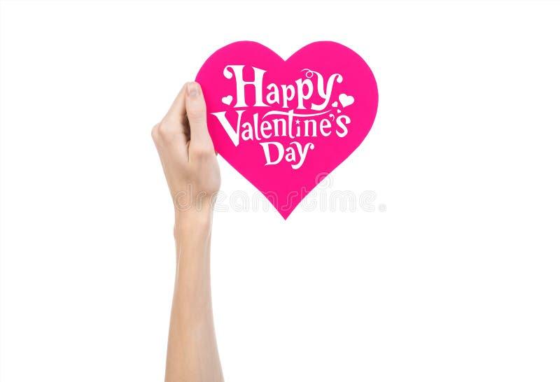 Thème de Saint-Valentin et d'amour : la main tient une carte de voeux sous forme de coeur rose avec la Saint-Valentin heureuse de photo libre de droits