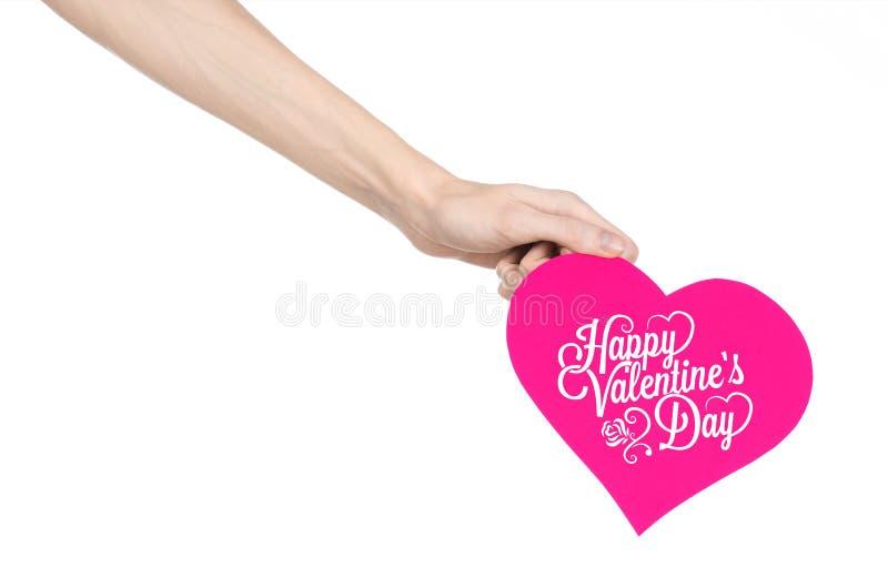Thème de Saint-Valentin et d'amour : la main tient une carte de voeux sous forme de coeur rose avec la Saint-Valentin heureuse de photographie stock libre de droits