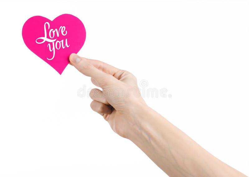 Thème de Saint-Valentin et d'amour : la main tient une carte de voeux sous forme de coeur rose avec les mots vous aiment a isolé images stock