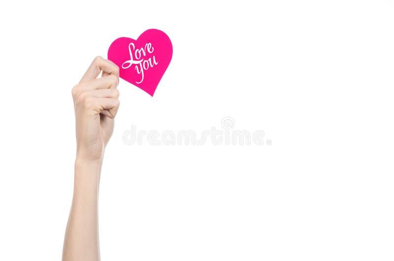 Thème de Saint-Valentin et d'amour : la main tient une carte de voeux sous forme de coeur rose avec les mots vous aiment a isolé photo libre de droits