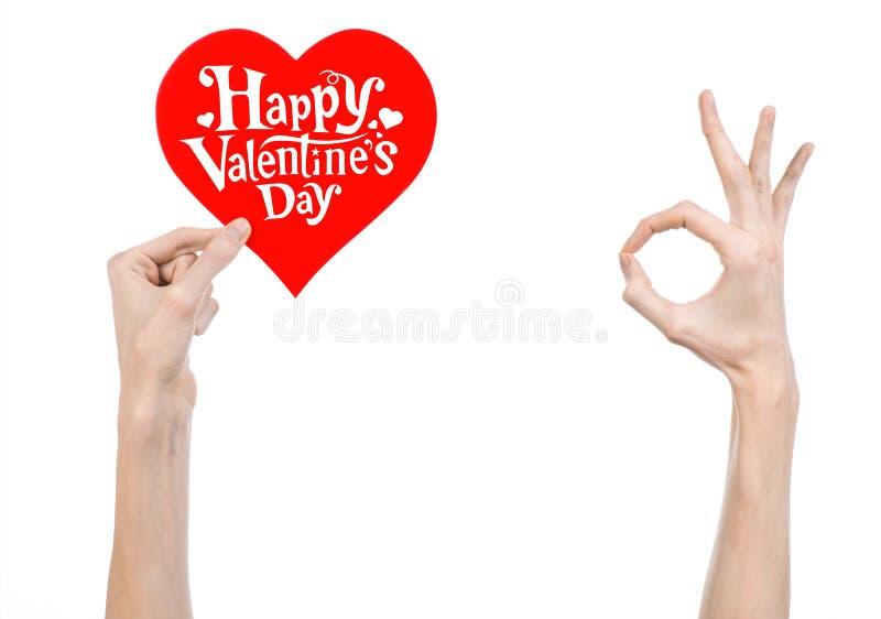 Thème de Saint-Valentin et d'amour : la main tient une carte de voeux sous forme de coeur rouge avec la Saint-Valentin heureuse d image stock