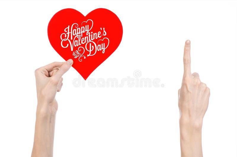 Thème de Saint-Valentin et d'amour : la main tient une carte de voeux sous forme de coeur rouge avec la Saint-Valentin heureuse d photographie stock
