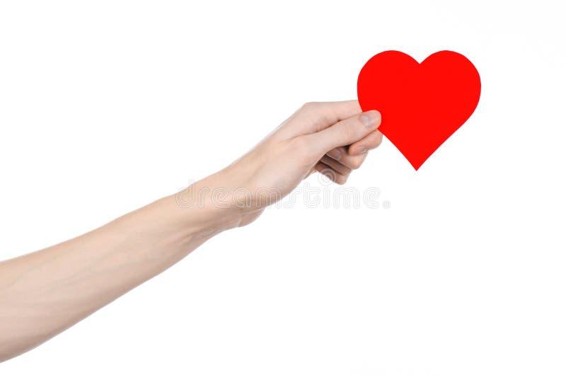 Thème de Saint-Valentin et d'amour : remettez juger un coeur rouge d'isolement sur un fond blanc photographie stock libre de droits