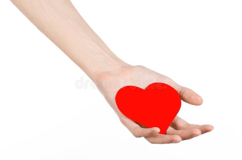 Thème de Saint-Valentin et d'amour : remettez juger un coeur rouge d'isolement sur un fond blanc photos stock