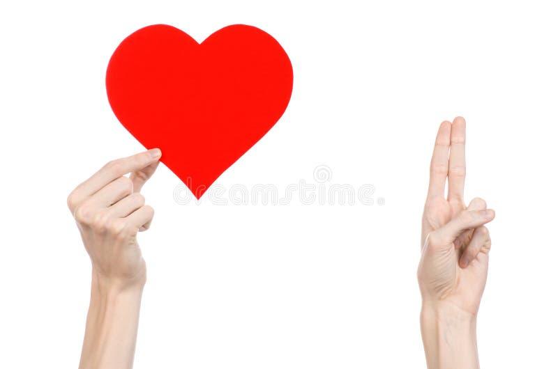 Thème de Saint-Valentin et d'amour : remettez juger un coeur rouge d'isolement sur un fond blanc images stock