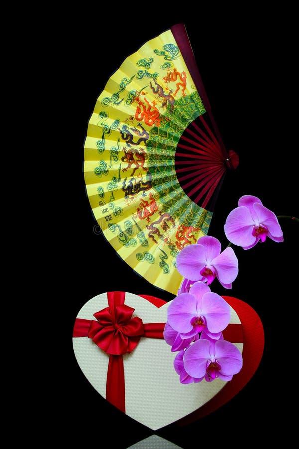 Thème romantique présentation de vie avec ventilateur rouge plié, boîte cadeau en forme de coeur et fleurs d'orchidées roses photos stock