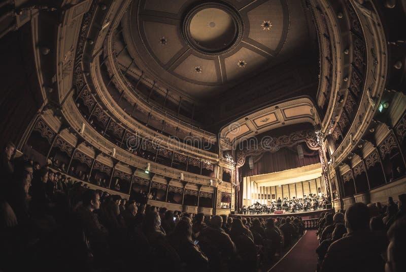 Théâtre complètement des personnes écoutant l'orchestre symphonique photographie stock libre de droits
