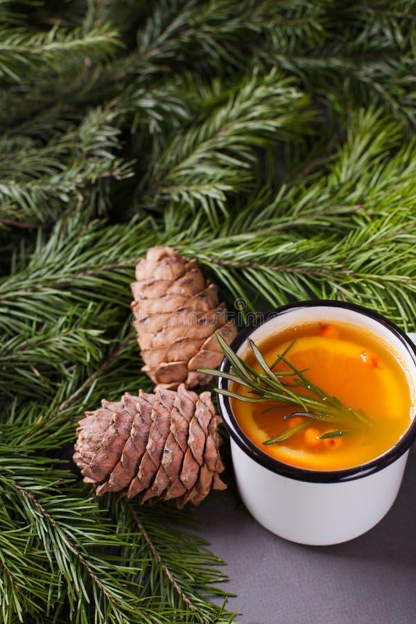 Thé à l'orange avec des cônes de mer-nerprun, de romarin, d'épice et de cèdre sous l'arbre de sapin photos stock