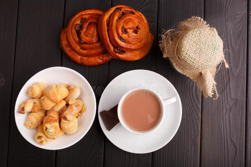 Thé au lait, un plat avec des bagels et deux petits pains Sur une table Vue de ci-avant indoors photos stock