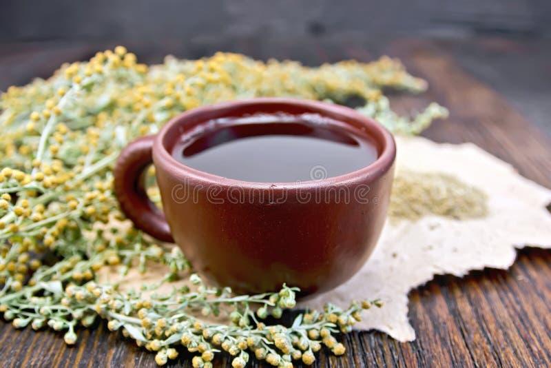 Thé avec l'absinthe dans la tasse d'argile à bord photographie stock libre de droits